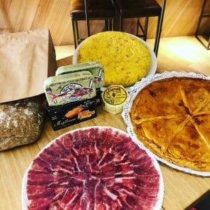 bolla de pan casero, latas de conservas gourmet, plato de jamón de bellota, una tortilla de patata y una empanada casera