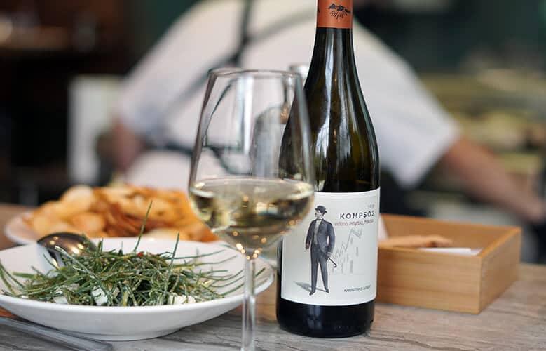 botella y copa de vino blanco con ensalada